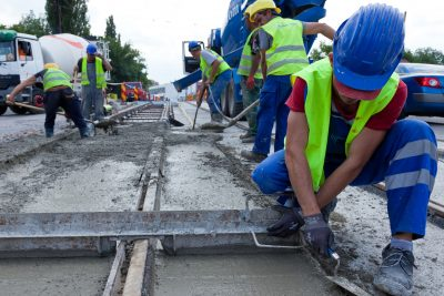 construction team pouring concrete on a road with boots and protection gear