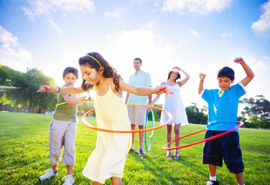 Family playing with hula hoops in a park
