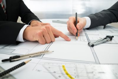 close-up of two architects planning project on blueprint