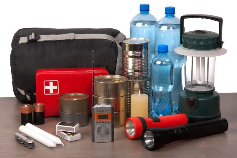 Survival kit with first aid, a lamo, water, non-perishable foods, matches, candle, walkie talkie, batteries and a knife