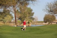 golf player in red shirt swinging a club from the fairway