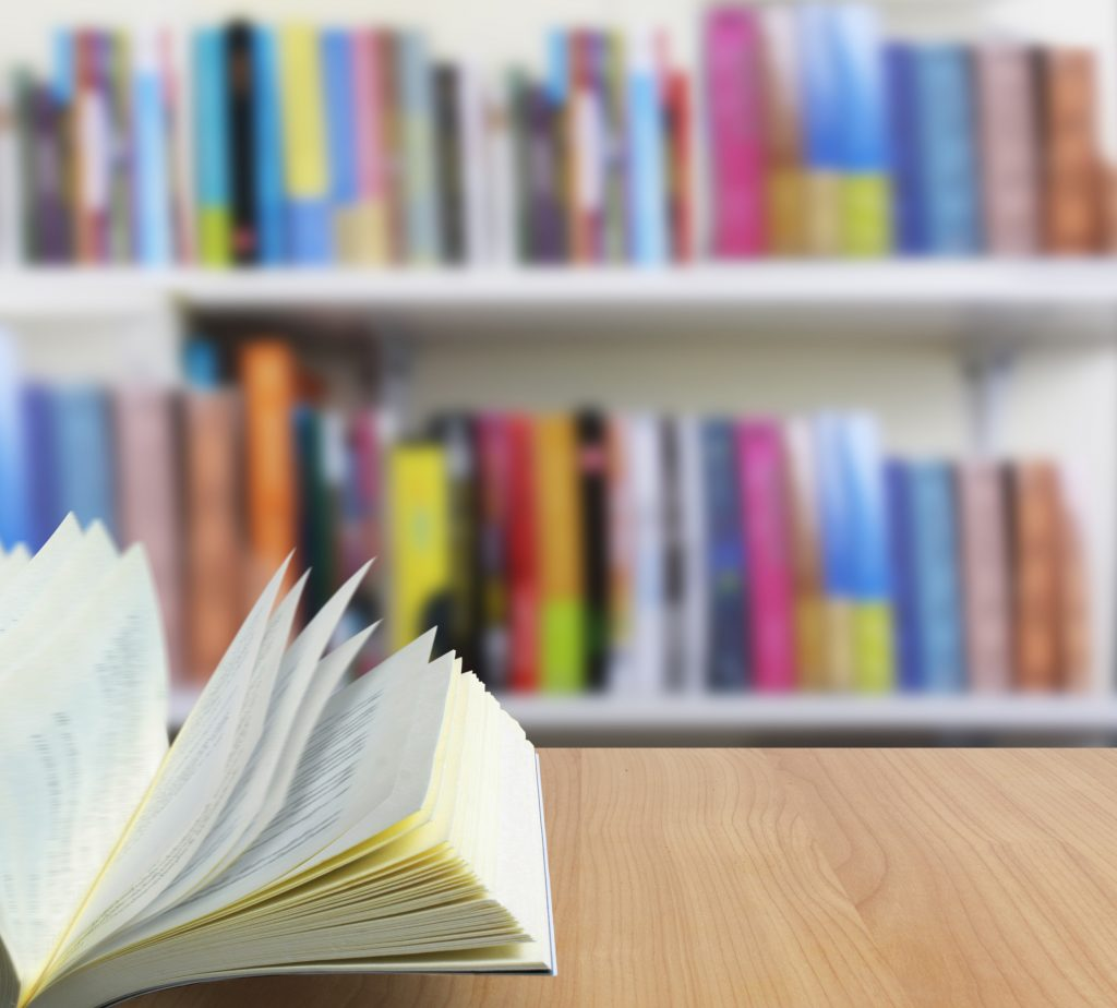 open book on table with books in the blured background