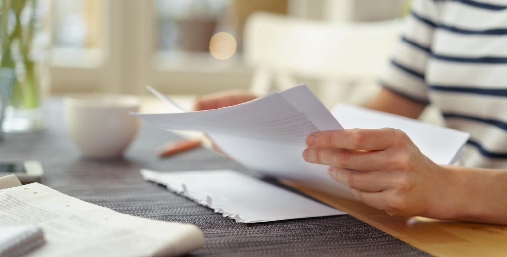 Person seated at a table with a cup of coffee reading a paper document