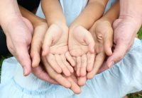 Two pairs of adult hands holding a child's hand