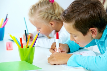 two kids drawing with colorful pencils