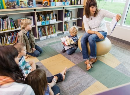 woman reading book to children in library