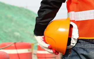 Construction worker holding hardhat on location site