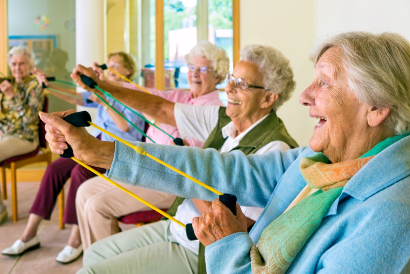 Large group of happy elderly ladies exercising in chairs doing stretching exercises