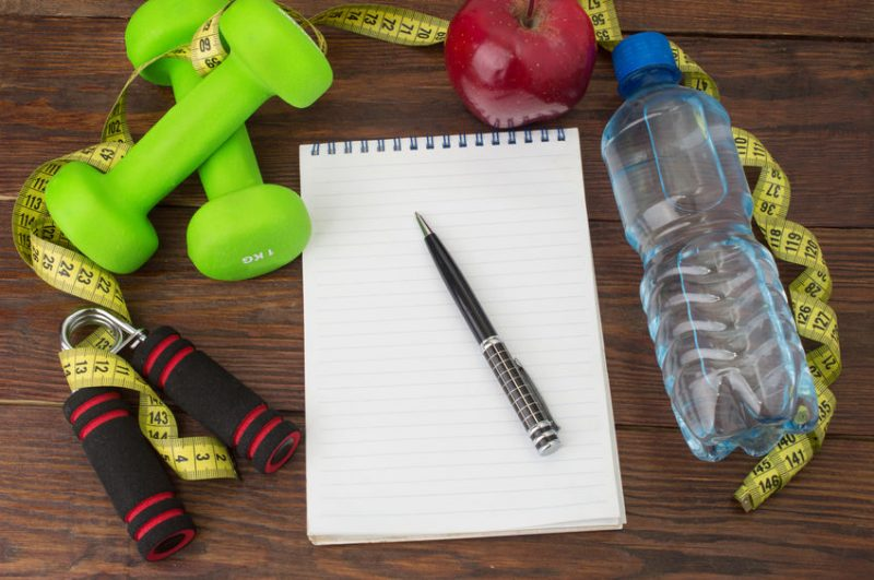 Workout and fitness items on table with pen and pape in the middle
