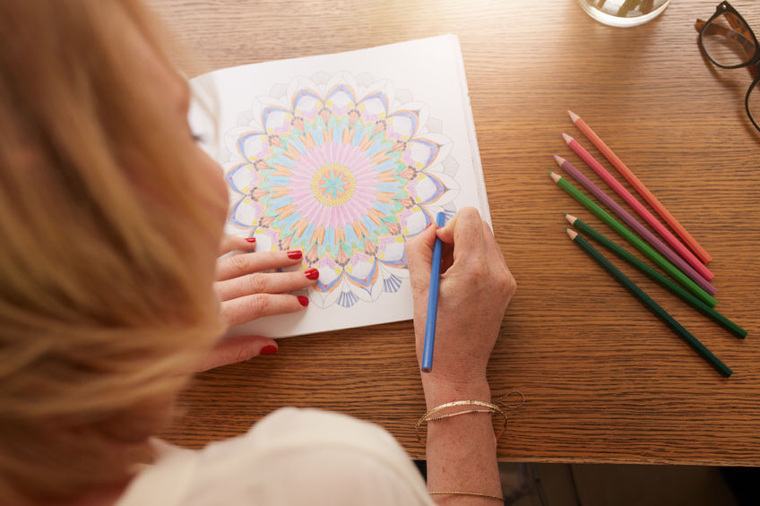 Woman coloring a mandala with wooden pencils