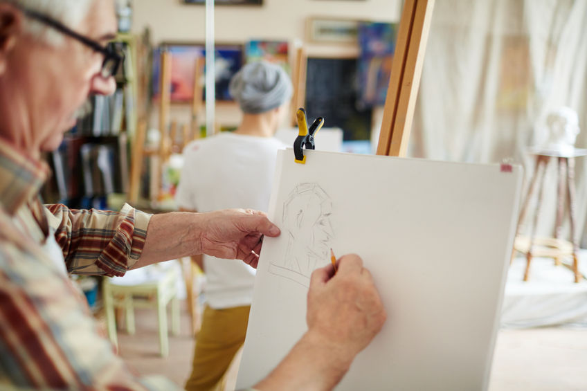 Man drawing on an easel in art class