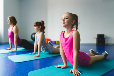 girls and instructor doing yoga in fitness class.