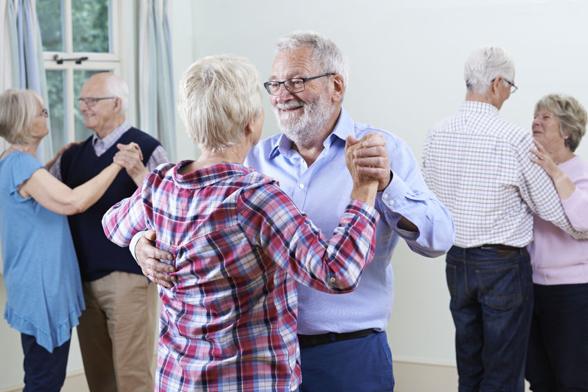 Group of seniors couple dancing indoors