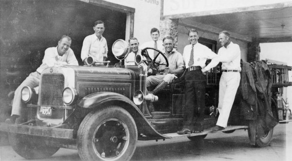 Antique black and white picture of seven men in uniform on a car