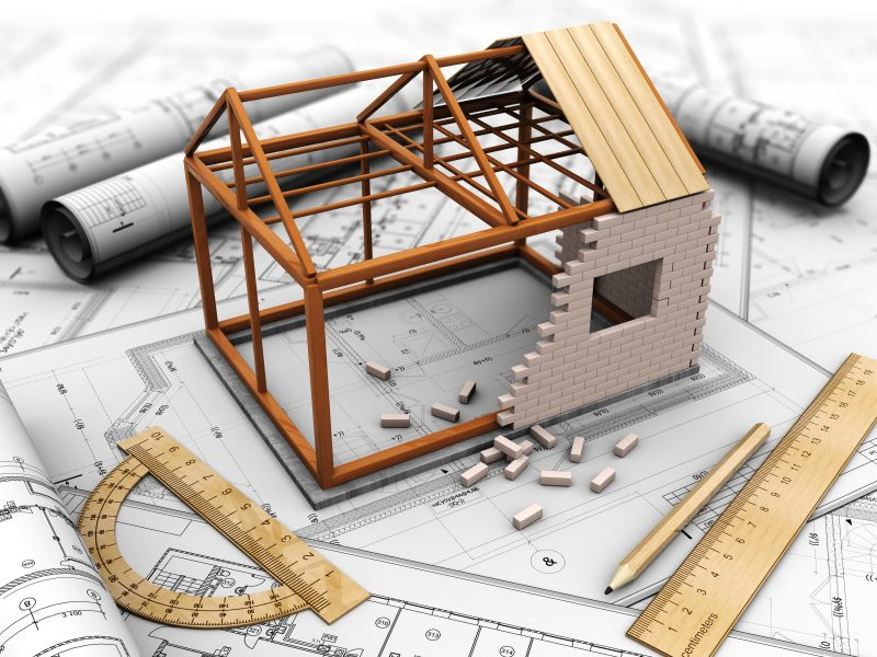 House project model on top of the blue print next to rulers and pencils