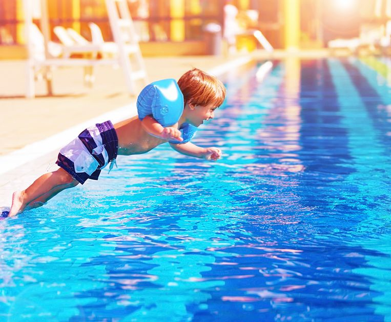 Small boy jumping to the pool