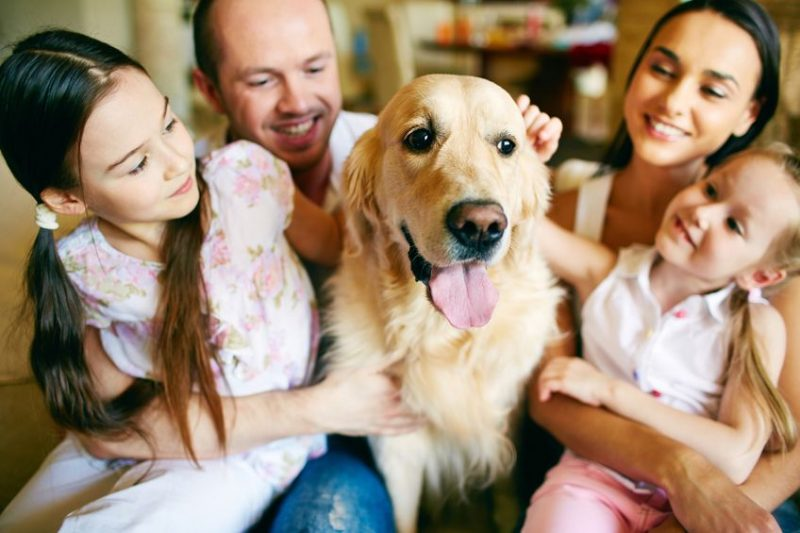 Family of four cuddling their dog