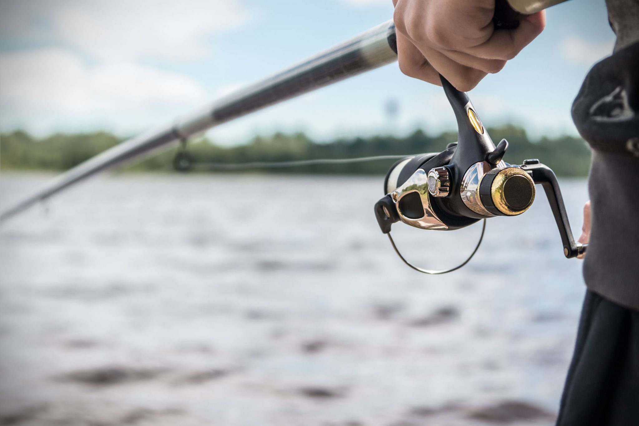 Hand holding a fishing rod and reel in front of a body of water
