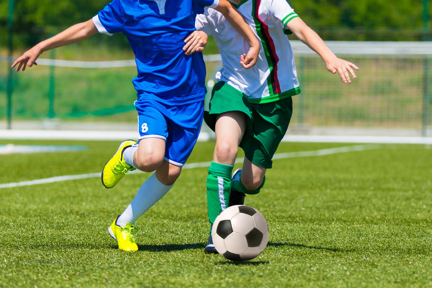 Two kids playing a soccer game outdoors