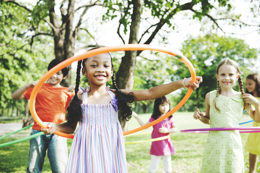 Children playing with hula hoops in the park