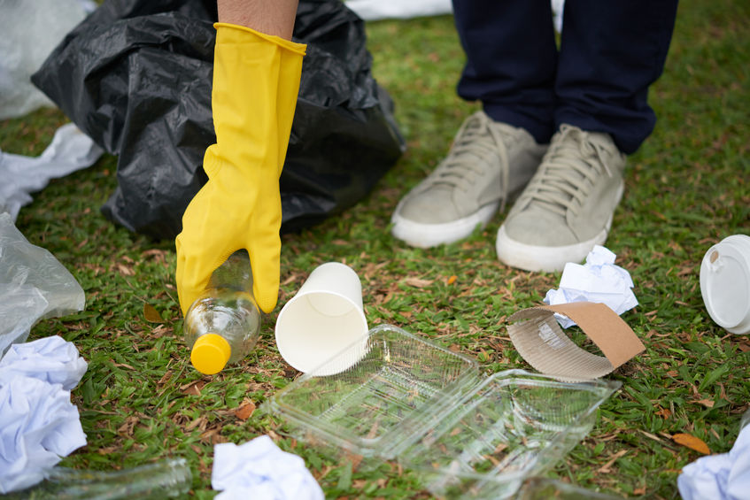 Plastic waste on grass being picked up with yellow gloves