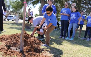Children planting a tree with adult supervision for Arbor Day