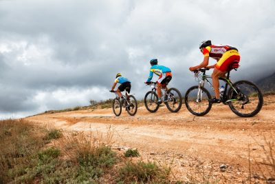 Three people bicycling outdoors