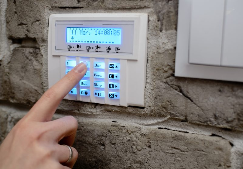 woman's finger entering code into the keypad of the alarm system