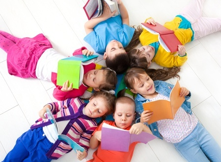 Children sitting in a circle reading individual books