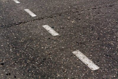 Asphalt with broken stripes painted on it