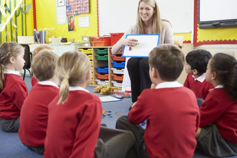 Teacher Teaching Spelling To Elementary School Pupils