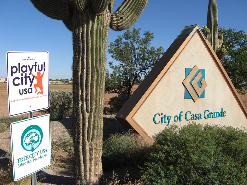City of Casa Grande welcome sign with playful city and tree city signs next to it