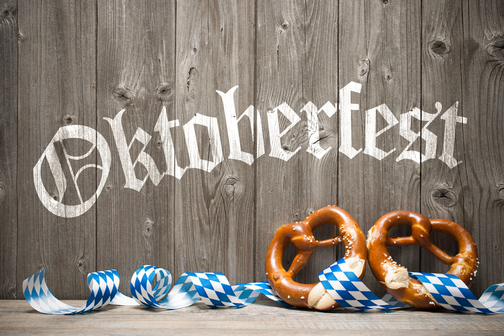 Wooden Oktoberfest sign with two bavarian pretzels and a ribbon