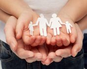 Two pairs of hands holding paper family cutout
