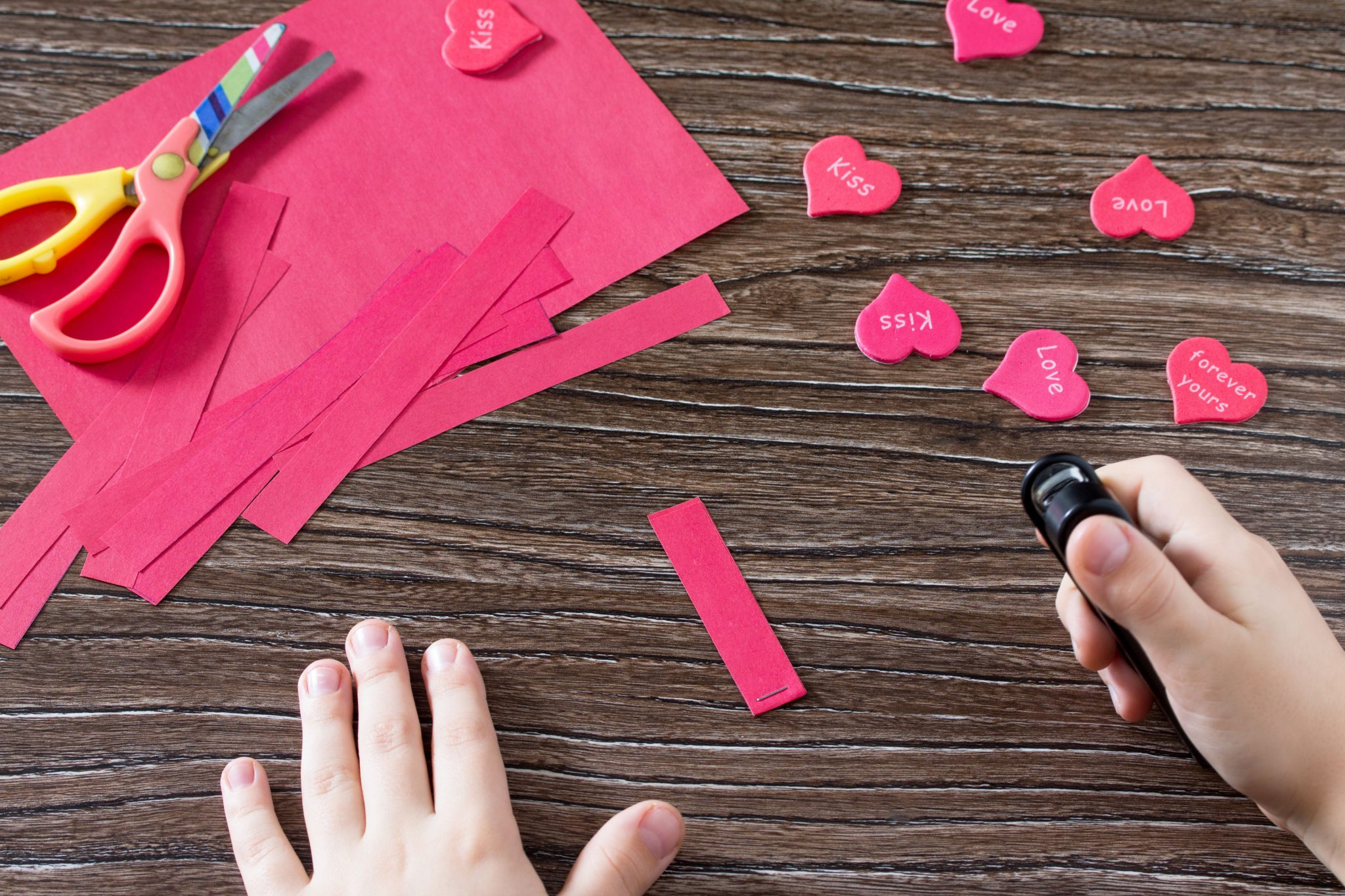 Child making valentines craft out of pink paper