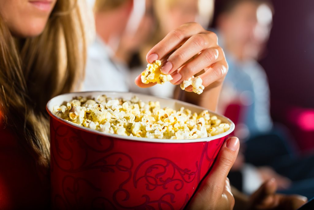 woman eating large container of popcorn in a movie theater