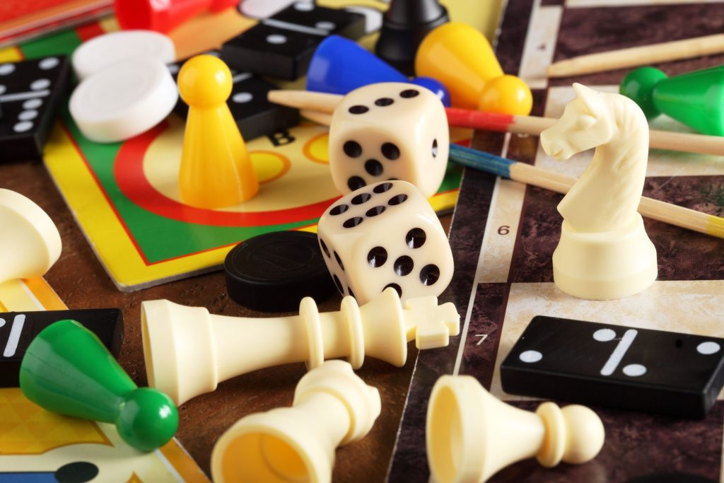 Board game pieces like pawns, chessmen, dominoes, dice, and boards