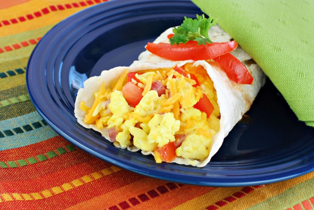 Breakfast burrito of egg, cheese, tomato, pepper and ham