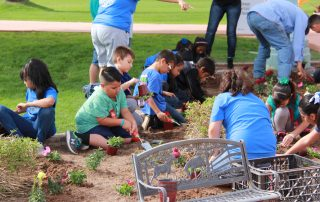 kids planting flowers at city hall