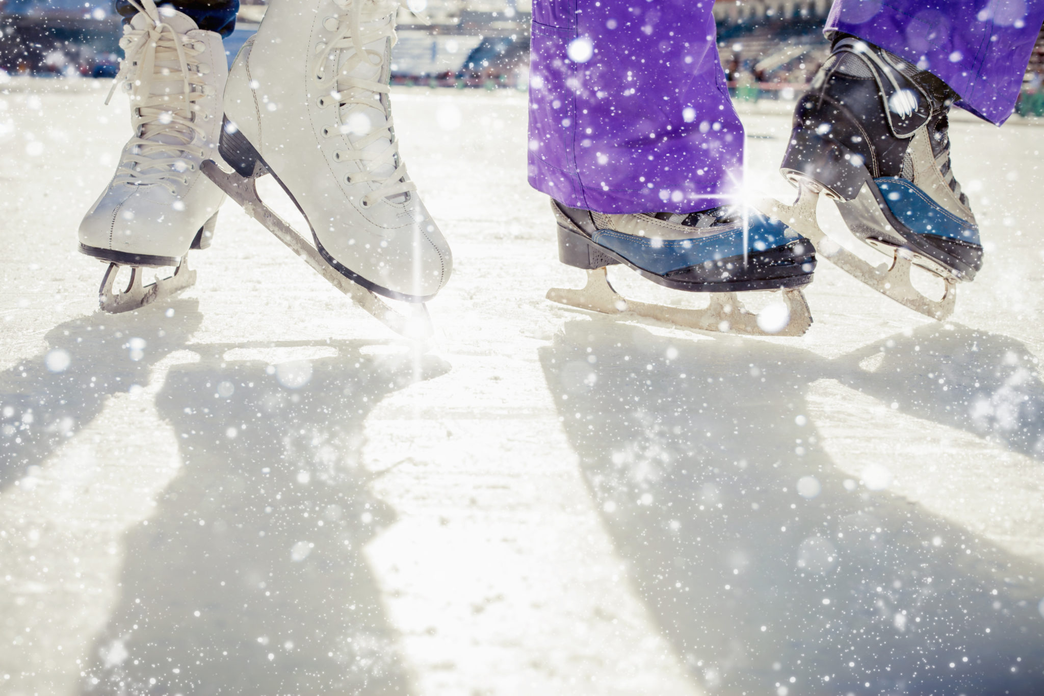 Pair is placed on ice skating. It is snowing outside