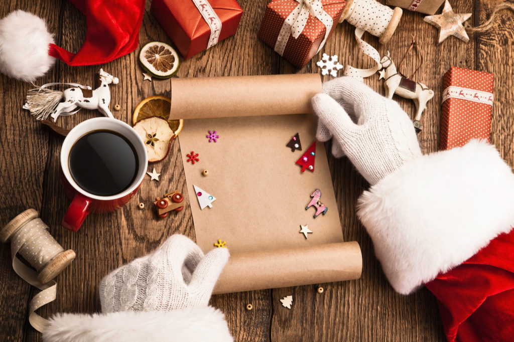 anta claus with gifts and wish list on wooden table