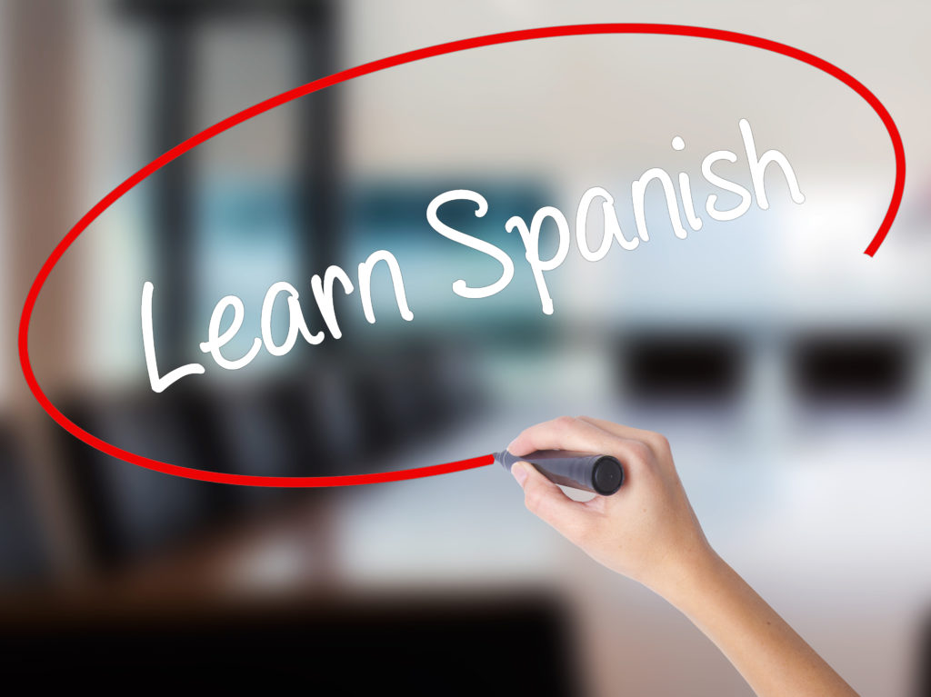 Woman Hand Writing Learn Spanish with a marker over transparent board.