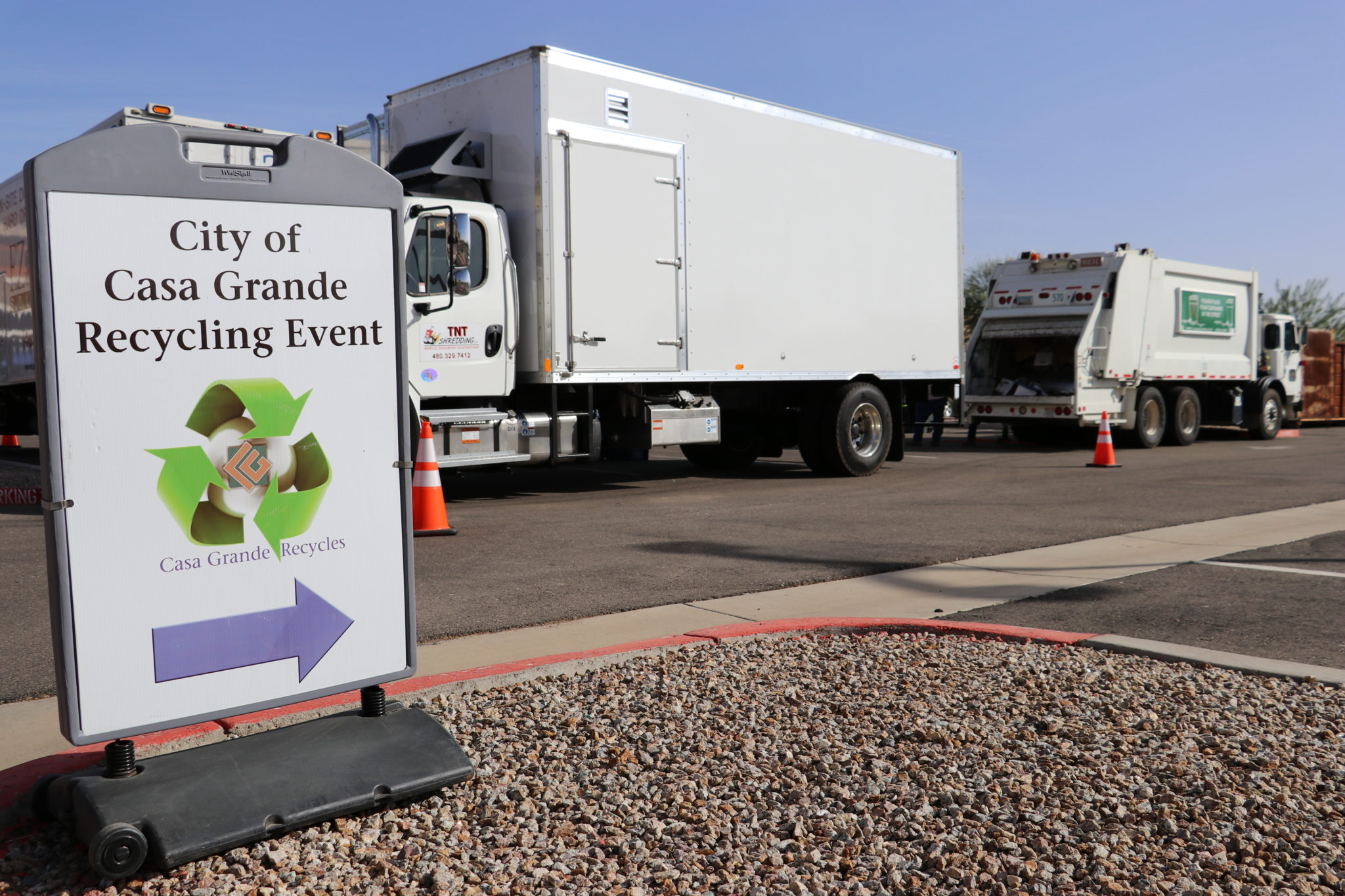 recycling truck behind directional sign