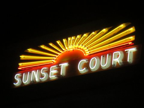 Sunset Court neon yellow and red sign at night