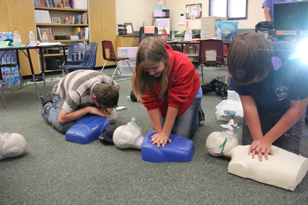 three kids performing CPR on dummies