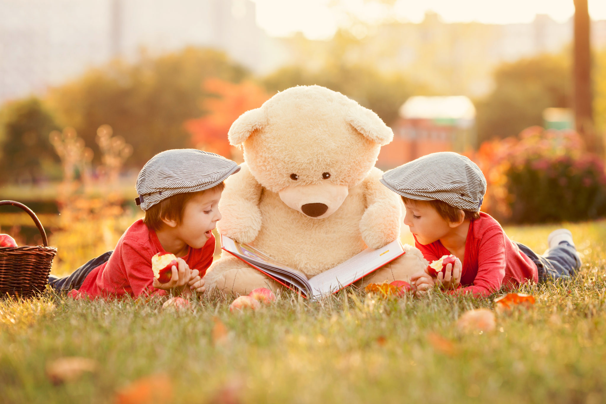 Two adorable little boys with his teddy bear friend in the park on sunset, nice back light