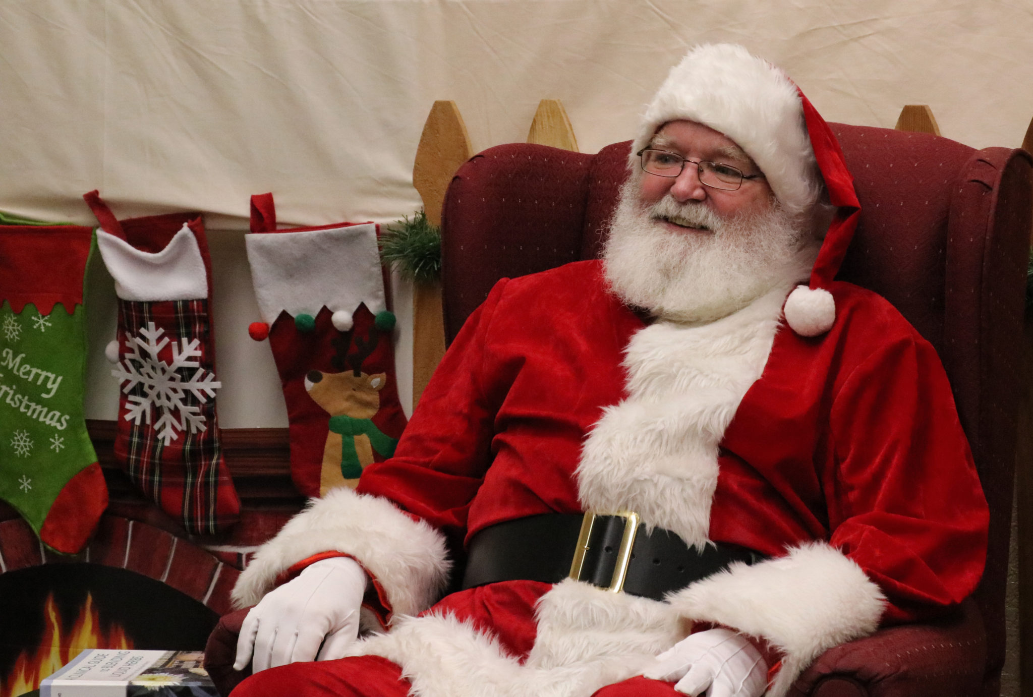 Santa Claus sitting in a big red chair with stockings hanging from a fake fire place