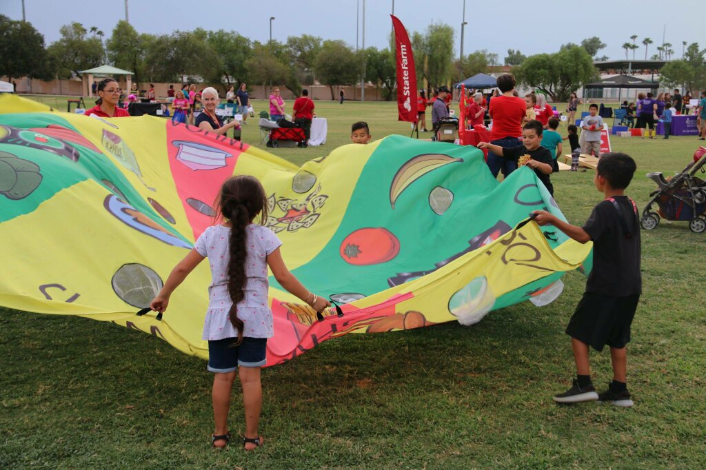 kids playing with large parachute and a ball that they fling in the air