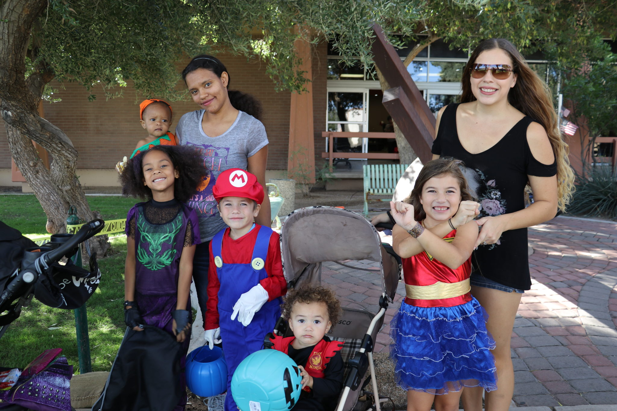 two mothers standing in line with their 5 kids all dressed up for halloween