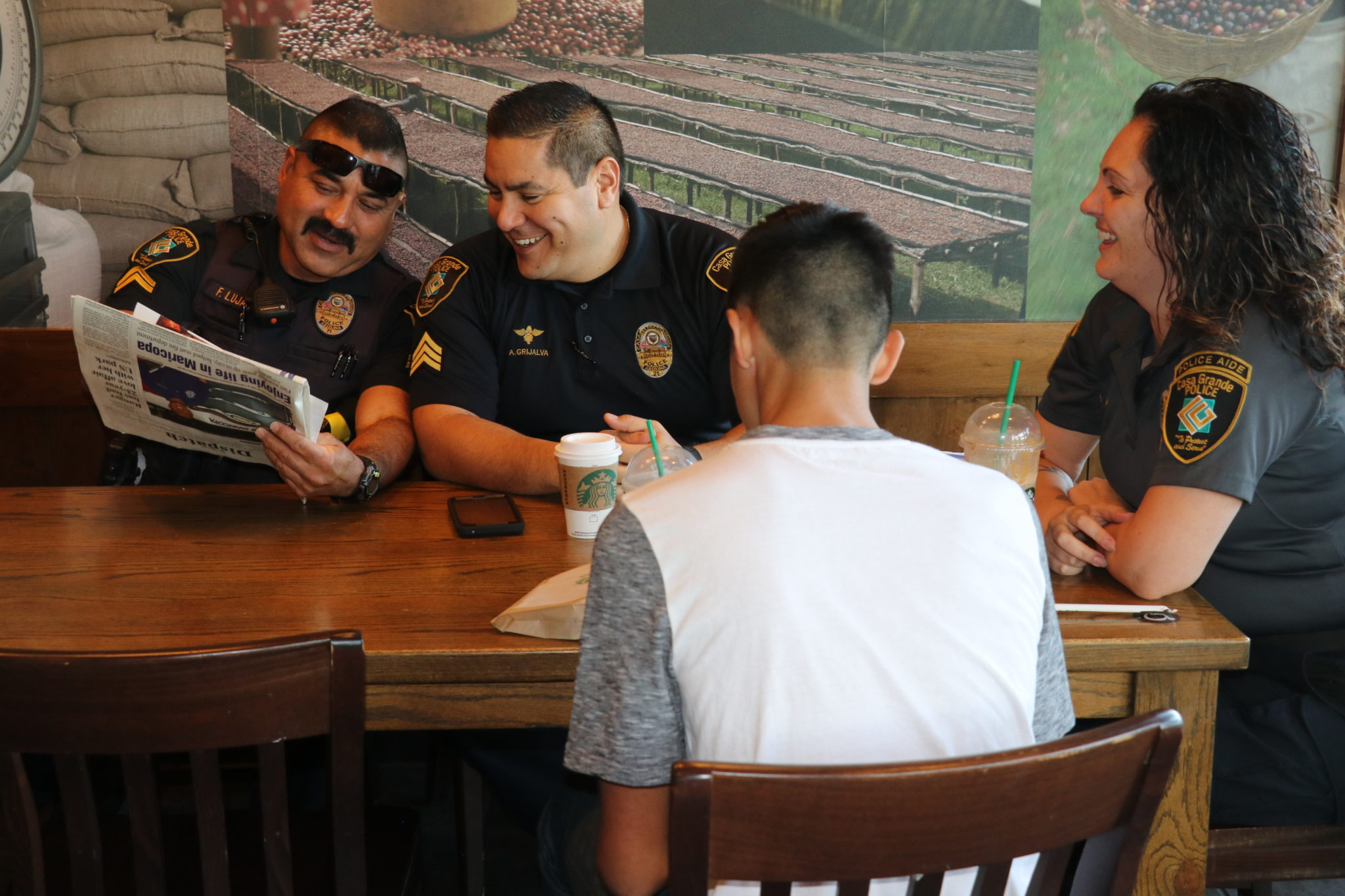 three cops laugh as they are reading the newspaper with one of their teenage sons sitting across from them at a coffee shop